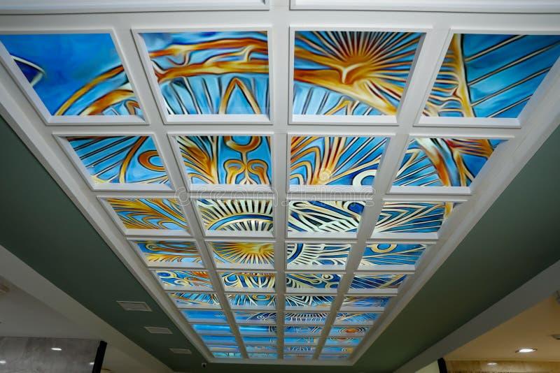 Blaues Buntglas auf der Decke in einem weißen Rahmen mit bunten handgemalten Mustern lizenzfreie stockfotografie