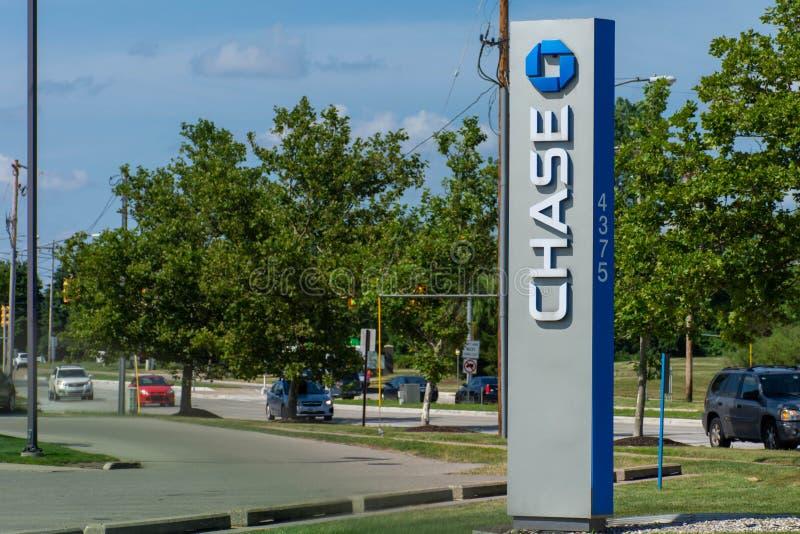 Blaues Chase Bank-Zeichen mit Antrieb durch, ATM und Blumen auf grünem Gras und blauem Himmel lizenzfreies stockfoto