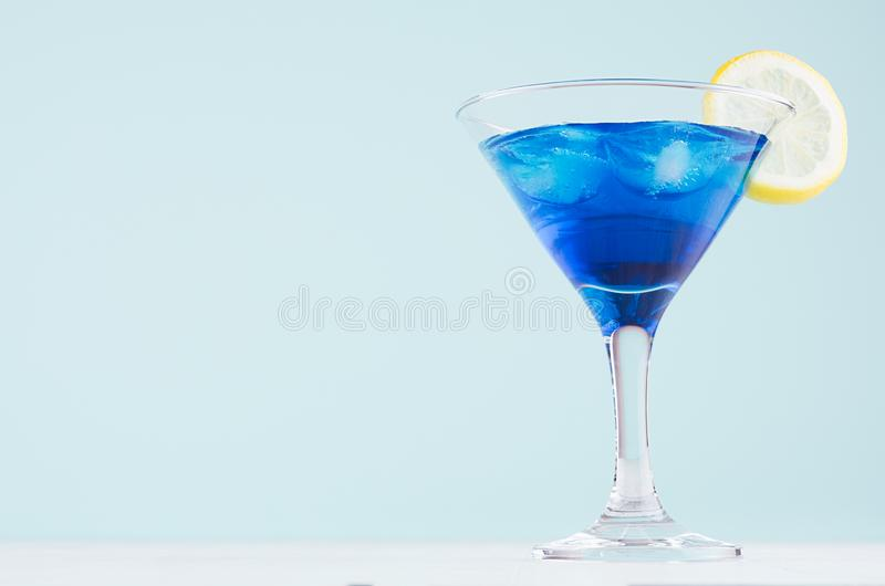 Blaues Curaçao-Cocktail mit Eiswürfeln, Zitronenscheibe in Luxus-Martini-Glas auf weißem hölzernem Brett und tadellose Farbpastel stockbild