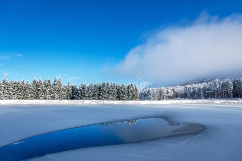 Blaues Eis und Sprünge auf der Oberfläche des Eises Gefrorener See unter einem blauen Himmel im Winter lizenzfreie stockfotos