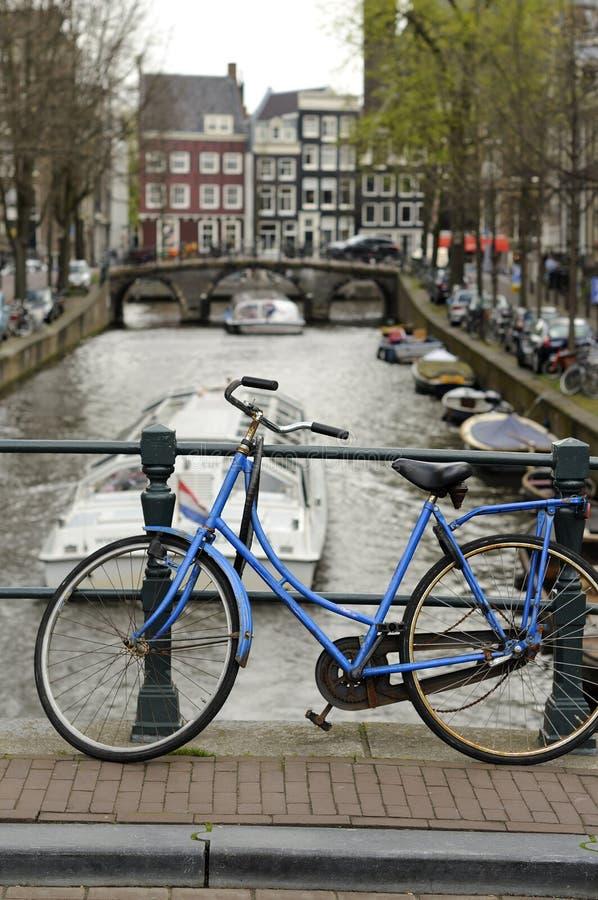 Blaues Fahrrad auf Kanal, Amsterdam lizenzfreies stockbild