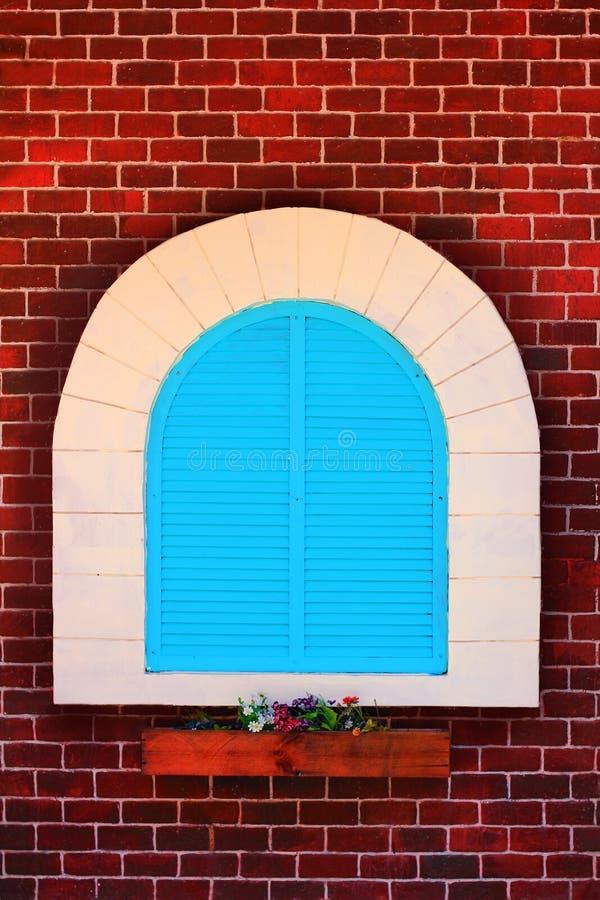 Blaues Fenster und alte Wandweinleseart des roten Backsteins, Tür mit Entwurfsbogen auf Wand und Hintergrund stockbild