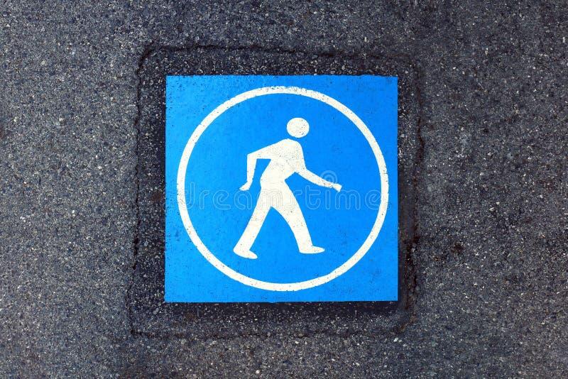 Blaues Fußgängerwarnzeichen auf der Straßendecke, gehen blaue Farbe auf Fußweg, Symbolfußgängerweg unterzeichnen am Bürgersteigsb lizenzfreies stockbild