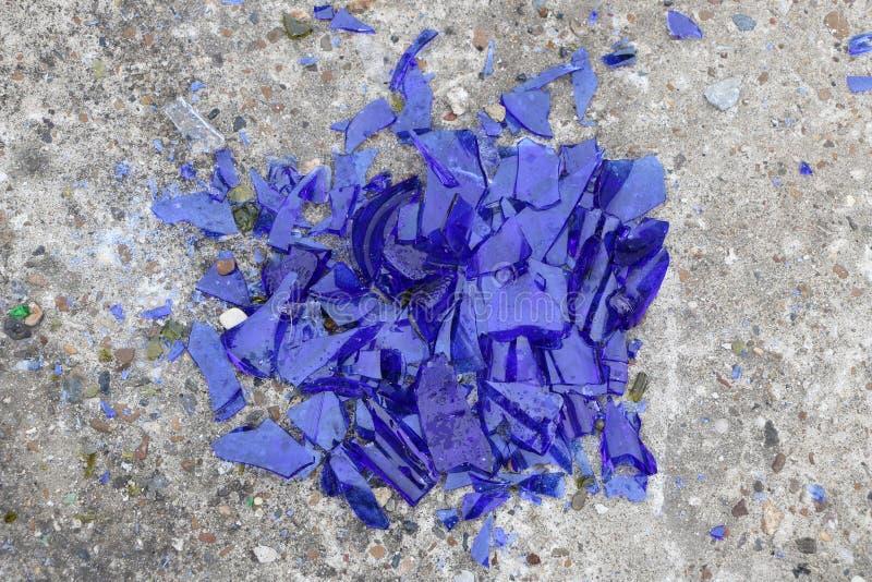 Blaues gebrochenes Glas auf einer Betondecke - Beschaffenheit für einen Hintergrund, Design stockfotos