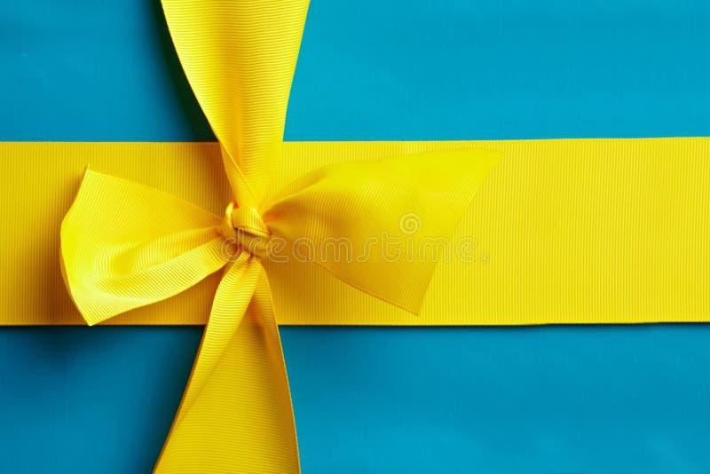 Blaues Geschenk mit gelbem Farbband stockbild