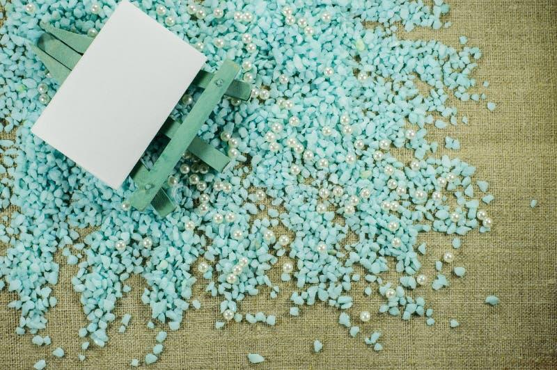 Blaues Gestell mit Weißbuch für Aufschriften auf dem zerfallenen blauen Kies lizenzfreie stockbilder