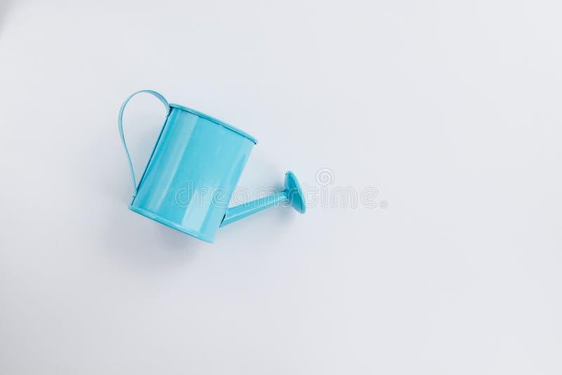 Blaues Gießkannespielzeug auf einem weißen Hintergrund Platz f?r Text Das Konzept der Landwirtschaft Ansicht von der Oberseite stockfotografie