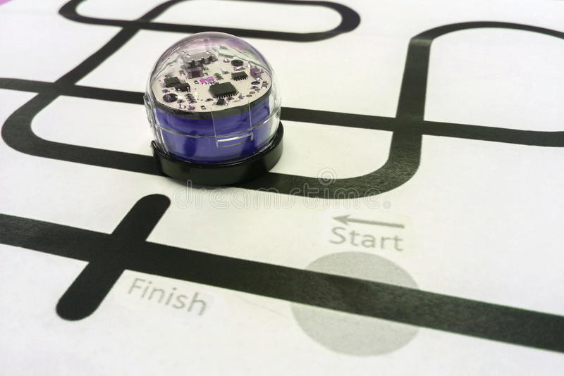 Blaues glänzendes Plastikmetallroboterauto wie programmiert, um auf schwarzer Linie des Weißbuches zu laufen lizenzfreies stockbild
