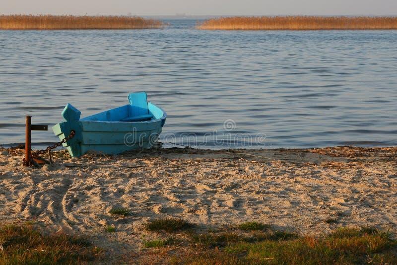 Blaues h?lzernes Boot auf dem sandigen Ufer gegen den See stockfotos