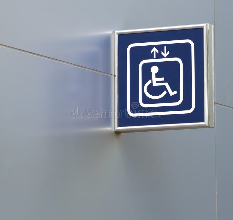 Blaues Handikap-Aufzugs-Zeichen auf metallischer Wand, Nahaufnahme lizenzfreie stockfotos