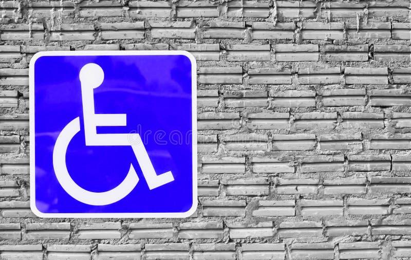 Blaues Handikapparken oder -rollstuhl auf Wandziegelstein lizenzfreie stockbilder