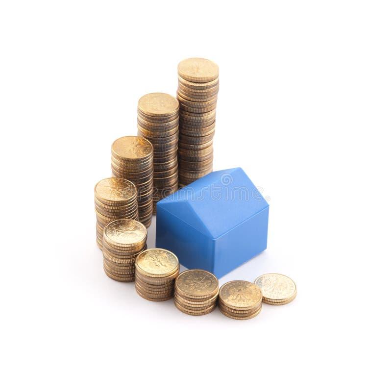 Blaues Haus mit Stapel Münzen lizenzfreie stockfotografie