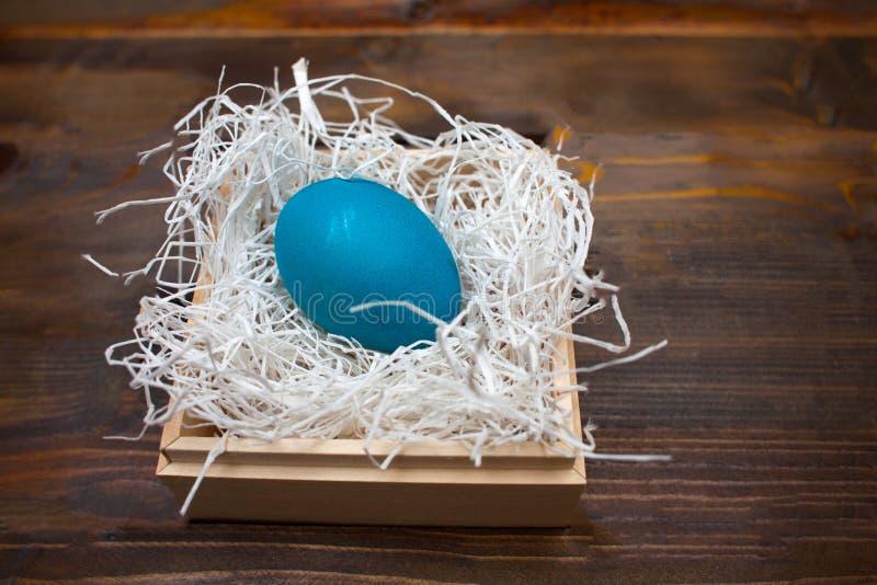 Blaues Huhn, gemaltes Ei für den Ostern-Feiertag in einem Kasten auf einem hölzernen Verwitterungshintergrund stockbild