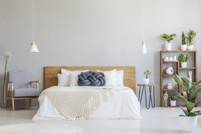 Blaues Knotenkissen auf hölzernem Bett im modernen Schlafzimmerinnenraum mit p lizenzfreies stockfoto