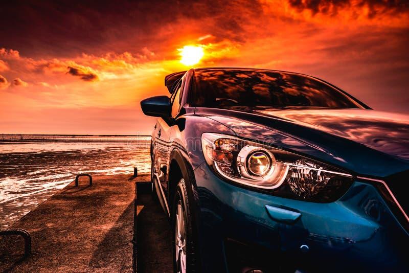 Blaues kompaktes SUV-Auto mit dem Sport, modernem und Luxusdesign parkten auf Betonstraße durch das Meer bei Sonnenuntergang Vord stockfotografie