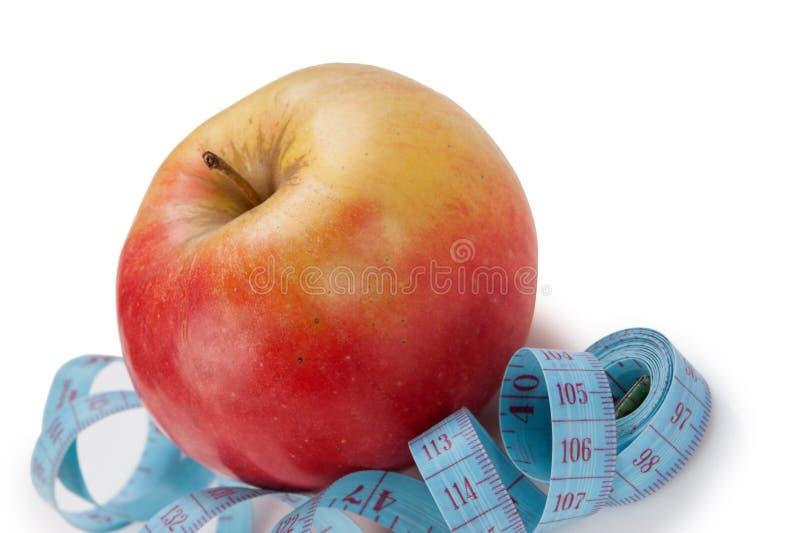 blaues Maßband und roter Apfel lokalisiert lizenzfreies stockbild