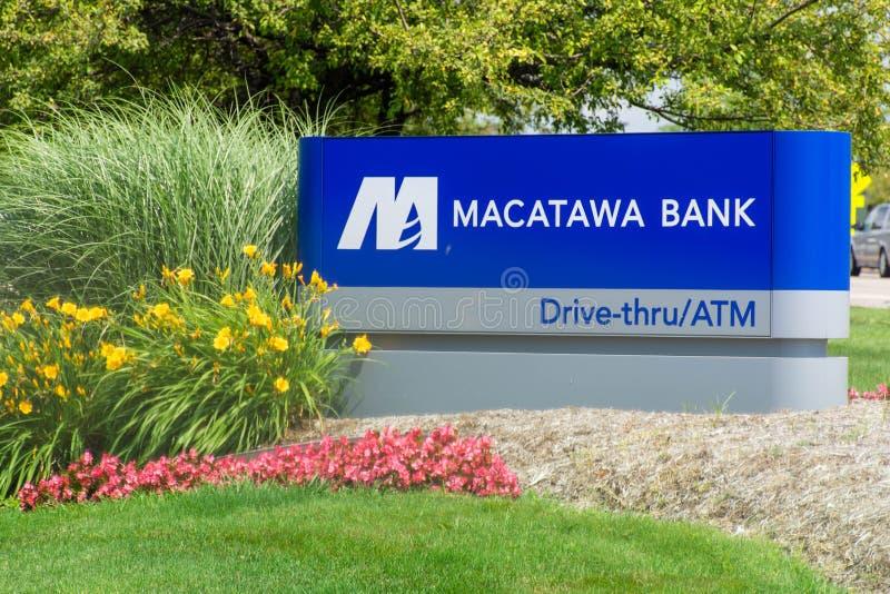 Blaues Macatawa-Bank-Zeichen mit Antrieb durch, ATM und Blumen auf grünem Gras und blauem Himmel stockfotos