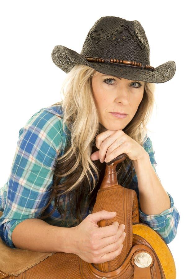 Blaues Mageres des schwarzen Hutes des Hemdes des Cowgirls auf dem Sattelblicklächeln stockfotos
