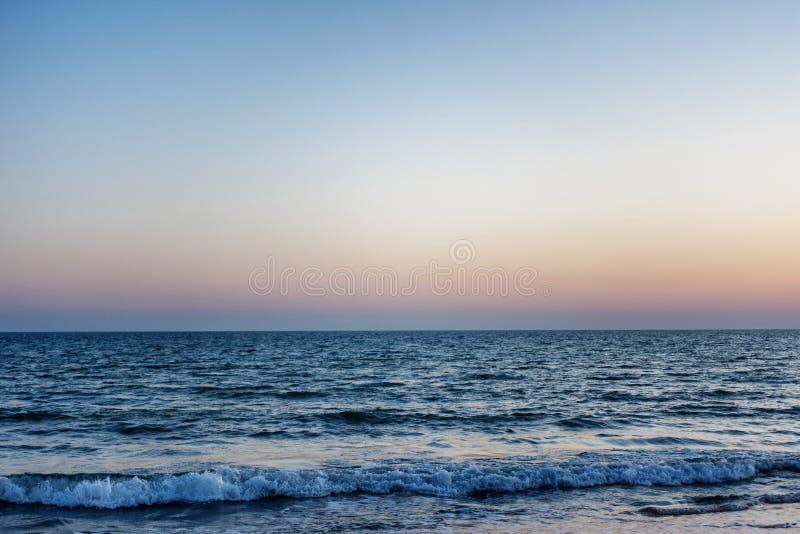 Blaues Meer bei Sonnenuntergang die Wellen sind zum Ufer Die Sonne über dem Horizont stockfoto