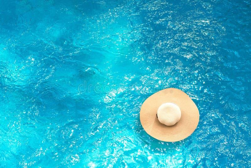 Blaues Meer, Himmel u Draufsicht des Strohhutes schwimmend auf Swimmingpool mit Sommerhintergrund Ferienzeit oder Feiertagslebens stockbild