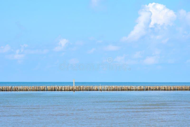 Blaues Meer im schönen Wetter dort sind die hölzernen Stöcke, die im Meer gestickt werden, um die Wellen zu entlasten Zu die Küst stockbild
