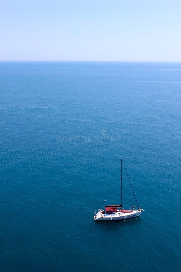 Blaues Meer und einsames weißes Boot lizenzfreie stockbilder