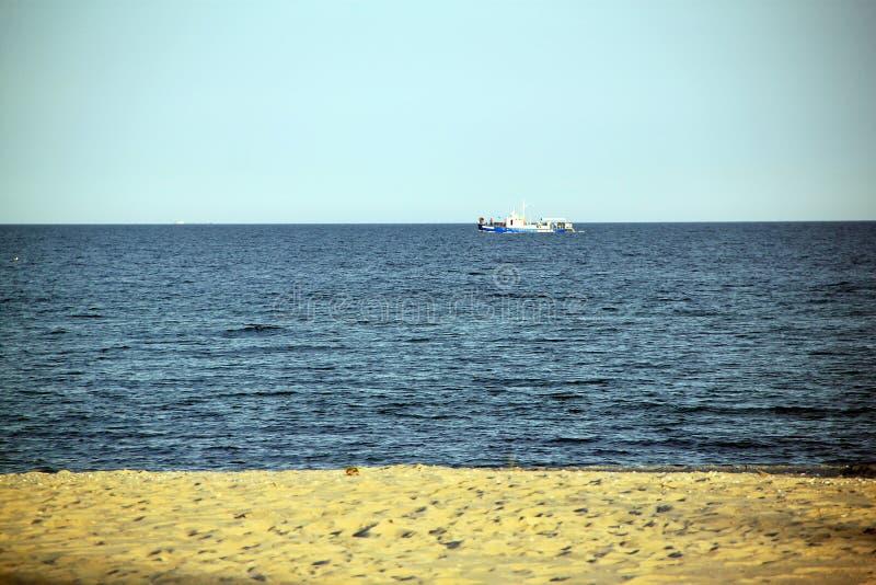 Blaues Meer, weißes Schiff mit gelbem Sand stockfotografie