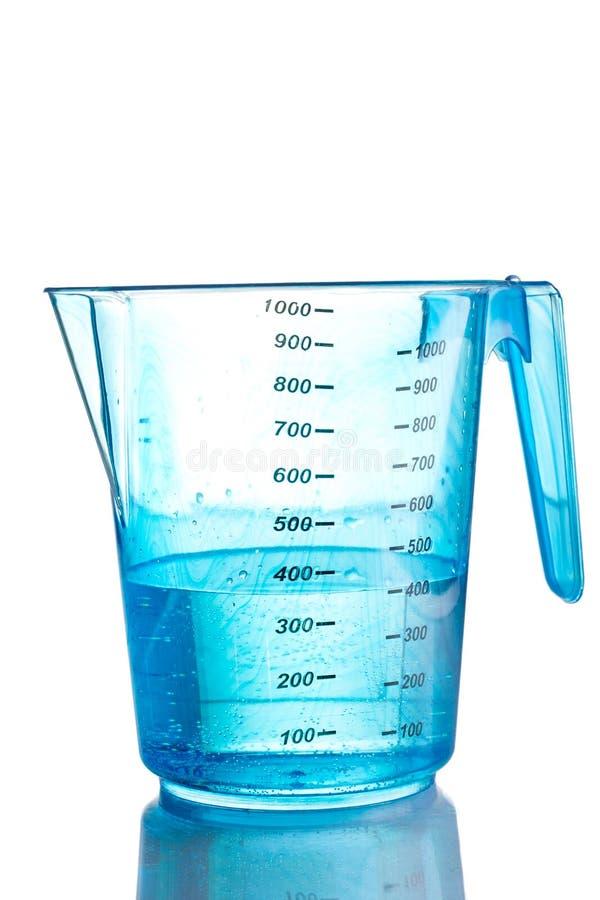 Blaues messendes Cup gefüllt mit Wasser stockfotos