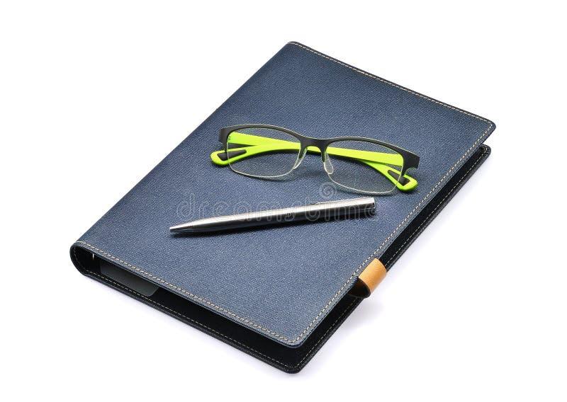 Blaues Notizbuch mit grünen Gläsern und Silber pe0n lokalisiert lizenzfreie stockfotos