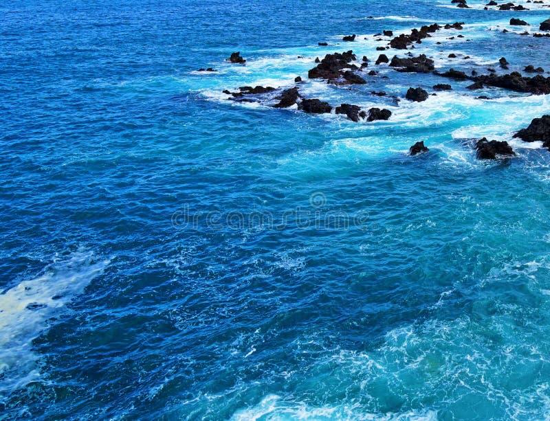 Blaues Ozeanwasser, mit Felsenriff im Hintergrund, Teneriffa lizenzfreie stockfotos