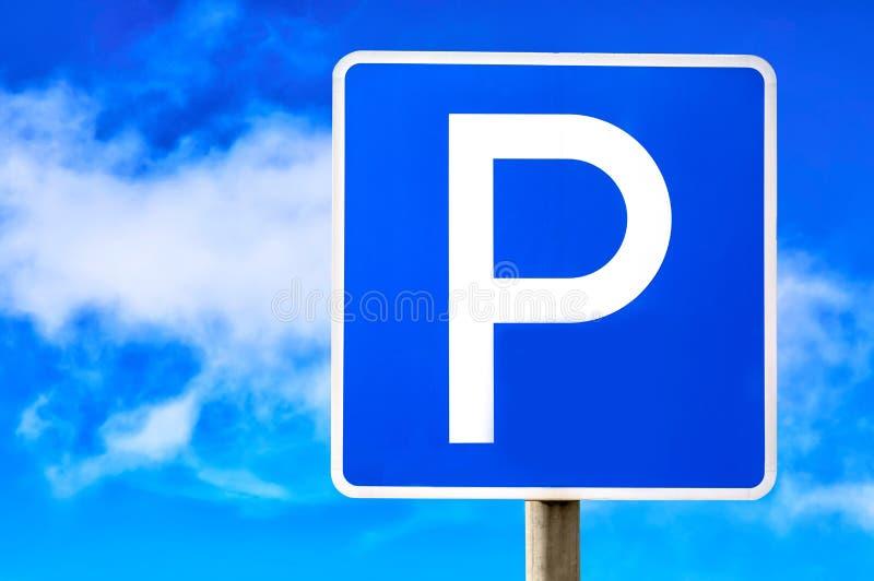 Blaues parkendes Zeichen gegen blauen Hintergrund des bewölkten Himmels lizenzfreies stockbild