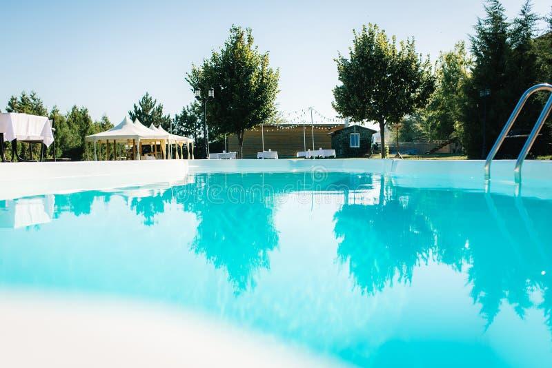 Blaues Pool im Freien im Garten umgeben durch Bäume stockfotografie
