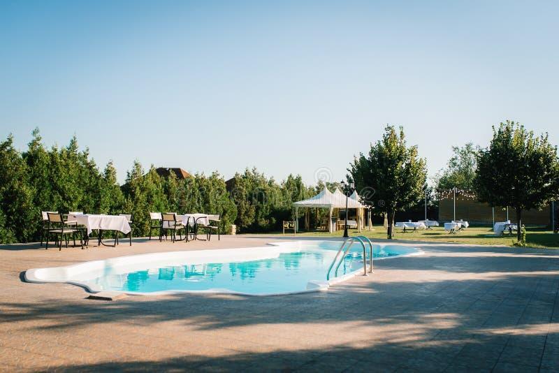 Blaues Pool im Freien im Garten umgeben durch Bäume lizenzfreies stockfoto