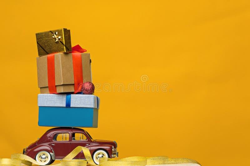 Blaues Retro- Spielzeugauto, das Weihnachten oder Neujahrsgeschenke, auf Gelb liefert lizenzfreie stockbilder