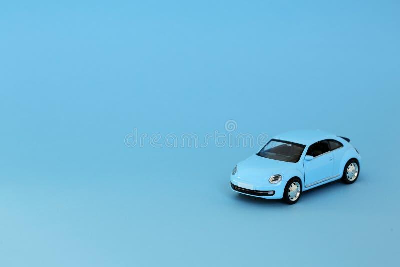 Blaues Retro- Spielzeugmodellauto auf blauem Hintergrund VW-Käfer in geworfenem Modell des Blaus Würfel lizenzfreies stockfoto