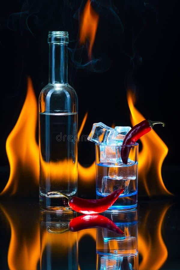 Blaues Schnapsglas voll vom Eis, wenig Flasche, zwei Hülsen rotes chil stockfotos