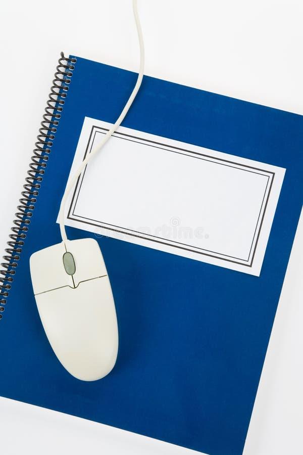 Blaues Schulelehrbuch und Computermaus stockfotografie