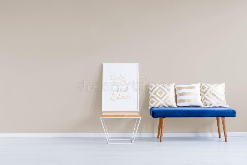 Blaues Sofa gegen Pastellwand lizenzfreies stockbild