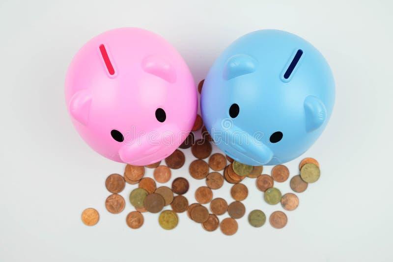 Blaues Sparschwein, das auf Münzen, Geldspareinlagenkonzept steht stockfotografie