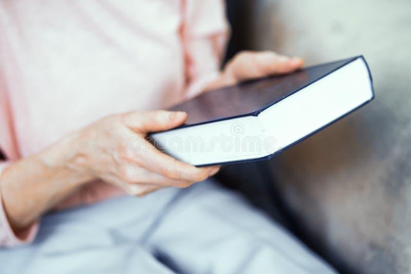 Blaues starkes Buch in den Händen einer älteren Frau lizenzfreies stockbild