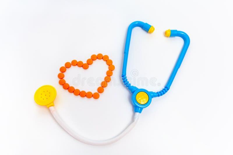 Blaues Stethoskop lokalisiert auf wei?em Hintergrund Stethoskop liegt auf Set Geld Kinderspielwaren durch Berufdoktor Ein Herz is lizenzfreie stockfotografie