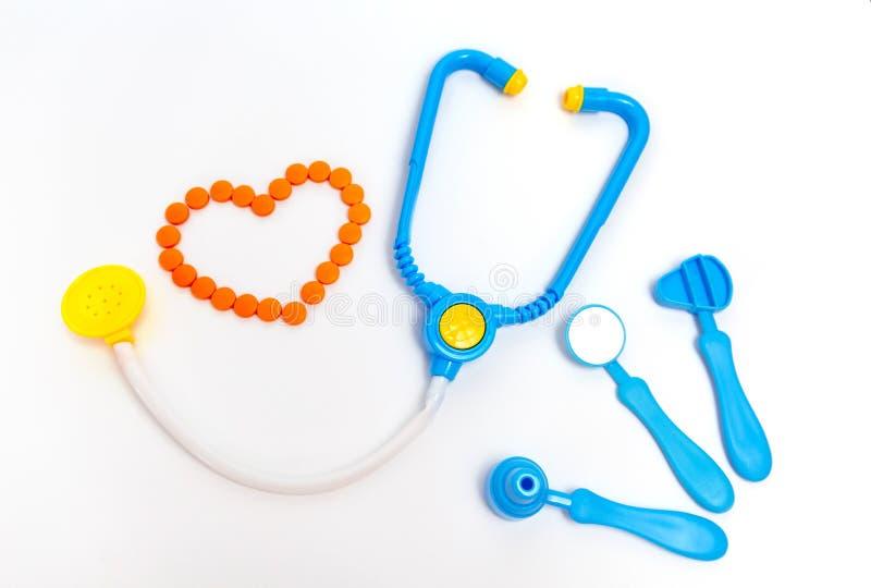 Blaues Stethoskop, Otoscope, Hammer, zahnmedizinischer Spiegel lokalisiert auf weißem Hintergrund Stethoskop liegt auf Set Geld D stockfoto