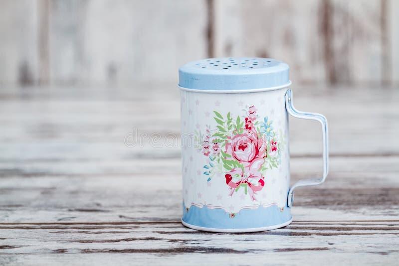 Blaues Tin Metal Powdered Sugar Shaker mit Blumenmuster lizenzfreies stockbild