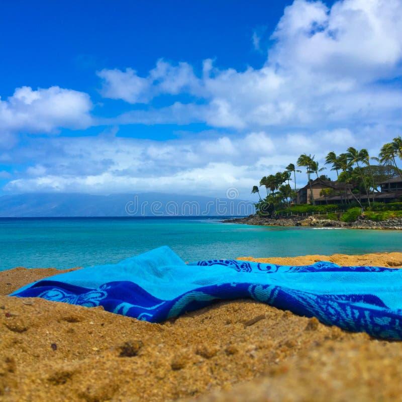 Blaues Tuch auf Strand mit Ansicht von Türkisozean lizenzfreie stockfotos