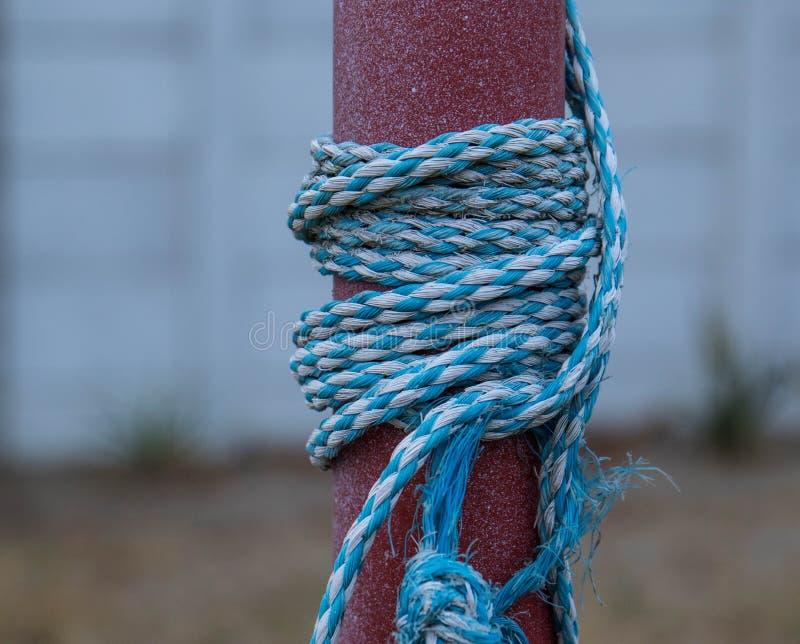 Blaues und weißes Seil knotete und Wunde um einen Pfosten lizenzfreie stockfotos