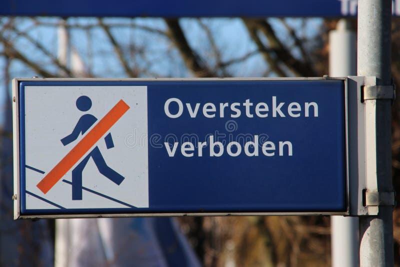 Blaues und weißes Zeichen mit niederländischem Sprachtext 'oversteken verboden 'der bedeutet, dass das das Übertreten der Schiene lizenzfreie stockfotografie