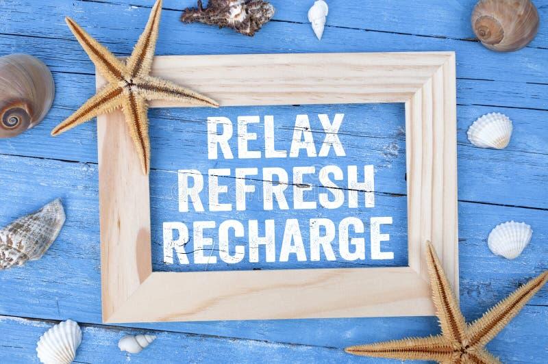 Blaues, verwittertes Holz mit mariner oder maritimer Dekoration und Reflex Refresh Recharge in einem Rahmen lizenzfreies stockfoto