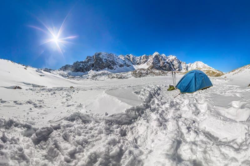 Blaues Zelt in den schneebedeckten Spitzen der Berge Weitwinkelpanorama stockfotografie