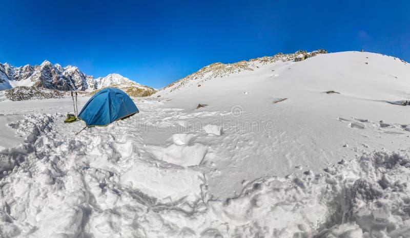 Blaues Zelt in den schneebedeckten Spitzen der Berge Weitwinkelpanorama stockbilder