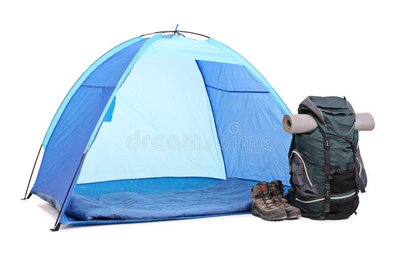 Blaues Zelt, grüner Rucksack und ein Paar Stiefel stockfoto